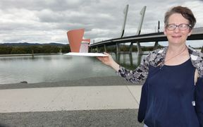 Photographer Diane Stoppard with the model of the camera obscura sculpture, in front of Whangarei's bascule bridge.