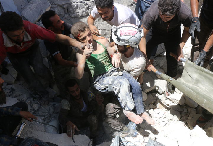 White Helmet volunteers carry a boy they rescued from rubble in Aleppo.
