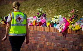 A Member of the Australian Red Cross counselling team walks past a makeshift floral tribute at the Dreamworld theme park on the Gold Coast.