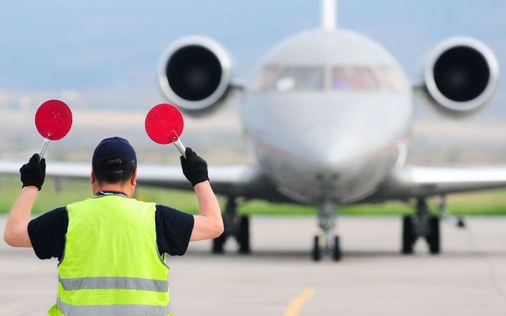 An air traffic controller guides a plane on a runway.