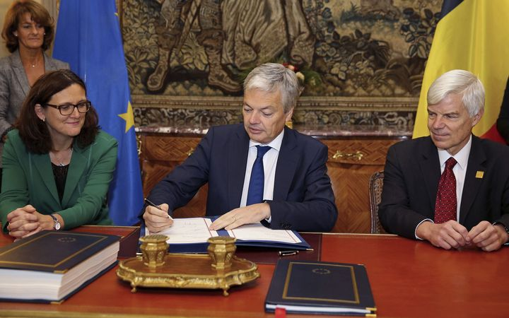 Vice-Prime Minister and Foreign Minister Didier Reynders (C) signs next to European Commissioner for Trade Cecilia Malmstrom (L) and Candian Ambassador Olivier Nicoloff (R) during the signing ceremony by Belgium of the EU-Canada Comprehensive Economic and Trade Agreement (CETA) on October 29, 2016
