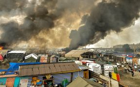 "Smoke rises from a fire over the ""Jungle"" migrant camp in Calais, northern France, on October 26, 2016, during a massive operation to clear the squalid settlement where 6,000-8,000 people have been living in dire conditions."