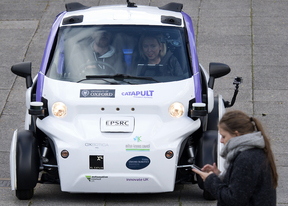 A woman uses a mobile phone as she walks in front of an autonomous self-driving vehicle, as it is tested in a pedestrianised zone, during a media event in Milton Keynes, north of London this month.