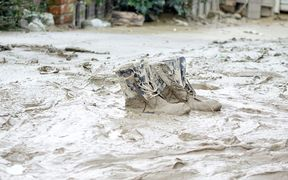 muddy boots surounded by floodwaters