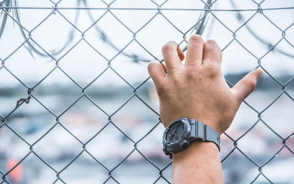 A prisoner's hand against a security fence at Paremoremo.