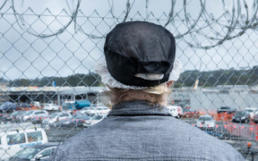 A prisoner looks out past a security fence at Paremoremo.