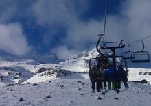 Skiers on a chairlift at Turoa ski field.