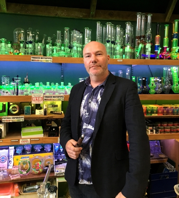 A portrait of Hemp Store owner and NORML NZ President Chris Fowlie in fromt of a range of pipes and vaporisers.