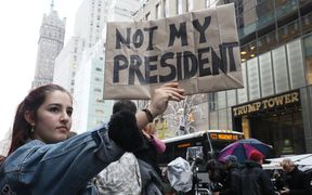 A woman (L) holding placard stating NOT MY PRESIDENT appeals her protest against the result of president election that Donald Trump will become the 45th President of the United States of America in next January, in front of the Trump Tower, Manhattan, New York on Nov.9, 2016