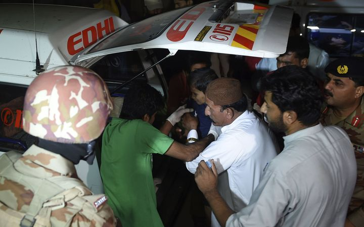 Volunteers move an injured blast victim from an ambulance at a hospital in the Hub district, some 40 kilometers from Karachi, Pakistan.