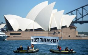 Members of Greenpeace hold up a sign  in front of the Opera House in Sydney on February 14, 2016.
