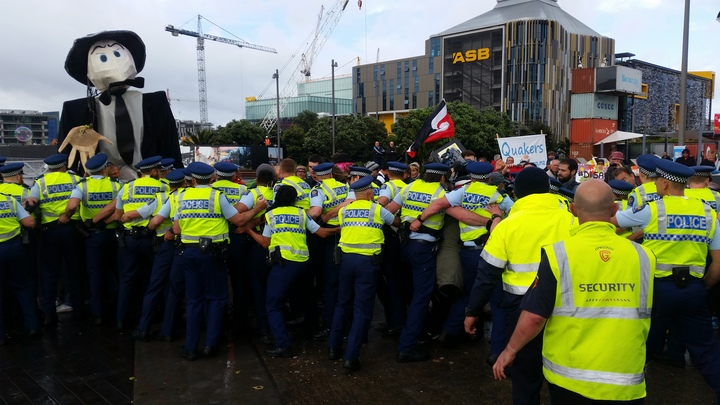 Police and protesters clash outside the annual defence forum in Auckland