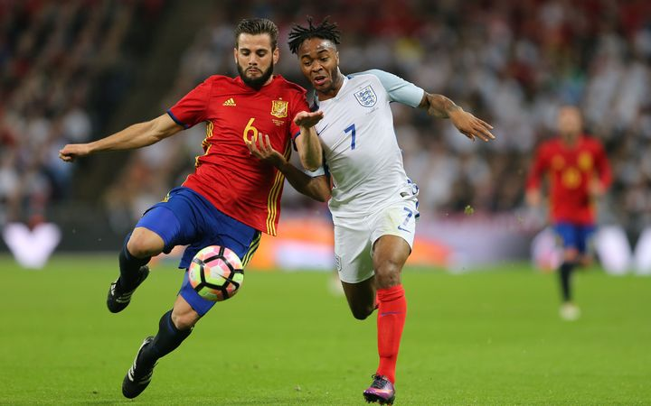 Nacho of Spain and Raheem Sterling of England battle for the ball.