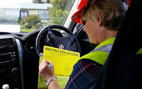 Marlborough district council building inspector Cherie Newman fills out a yellow restricted access placard for a badly damaged house in Ward, south Marlborough .