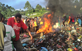 A photo taken on February 6, 2013 shows a crowd watching as a young mother accused of sorcery, is stripped naked, reportedly tortured with a branding iron, tied up, splashed with fuel and set alight on a pile of rubbish topped with car tyres, in Mount Hagen city in the Western Highlands of PNG.