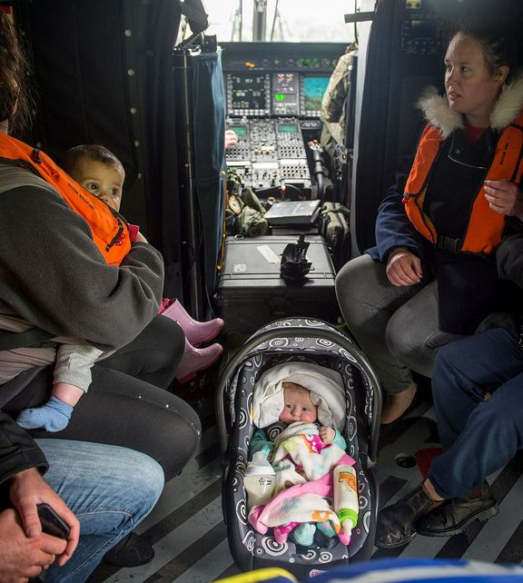 small baby in car seat sits between adults on a helicopter floor