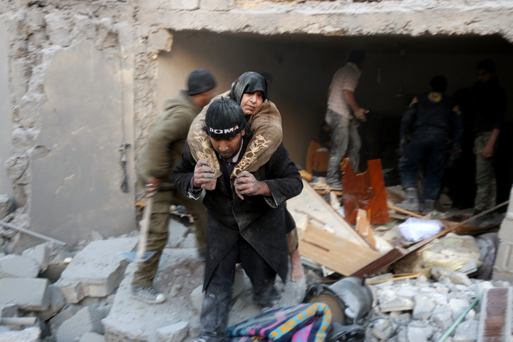 A rescuer carries a woman from the rubble of a building in Aleppo's rebel-held district of al-Hamra on 20 November.