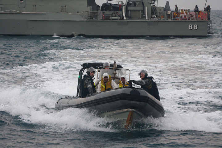 Australian navy personnel transfer Afghanistan asylum-seekers to a Indonesian rescue boat near Panaitan island, West Java on August 31, 2012 after the refugee's boat sunk.