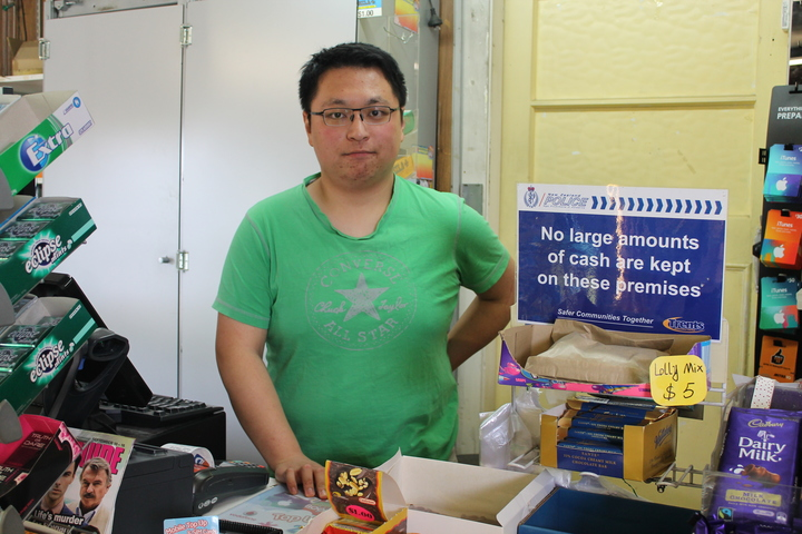 A photo of Adam Du at the counter of the Burwood's Lake Terrace Stationery and Dairy which was robbed earlier this year.
