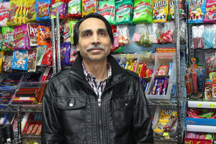 A photo of Kamlesh Patel in front of the sweet selection in his Opawa dairy. His shop has been robbed four times in seven years