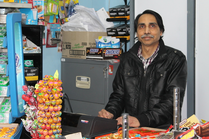 A photo of Kamlesh Patel at his counter. Earlier this year he fought with a robber who was trying to open his cigarette shutter.