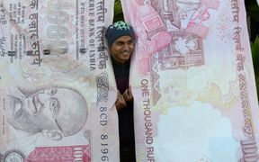A man poses with replica prints of the demonetised 500 and 1000 rupee notes as part of a street art exhibition in Mumbai November 20, 2016.