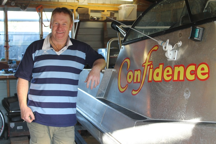 Kaikoura bach owner, Mark Boomer, with his fishing boat, Confidence.