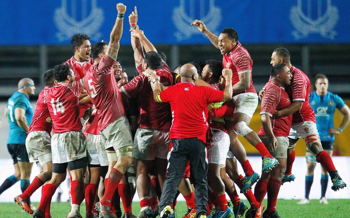 The Tonga rugby team celebrates their win over Italy