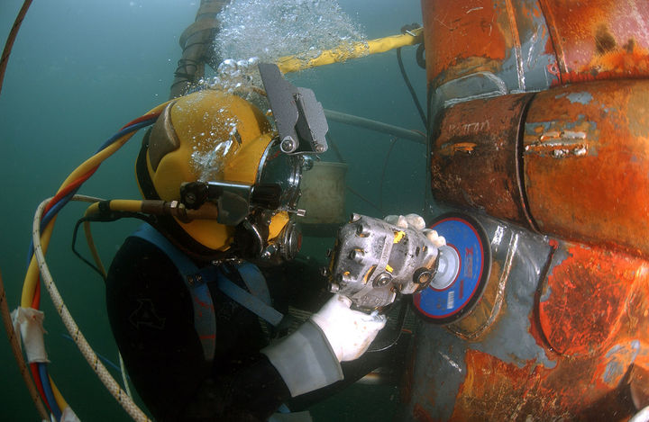Navy diver using an angle grinder underwater on a segment of piping
