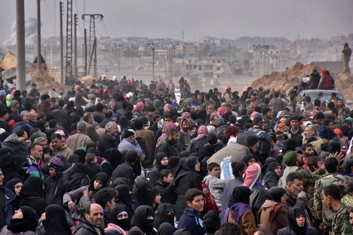 Syrian families, fleeing from various eastern districts of Aleppo, queue to get onto governmental buses on November 29, 2016 in the government-held eastern neighbourhood of Jabal Badro