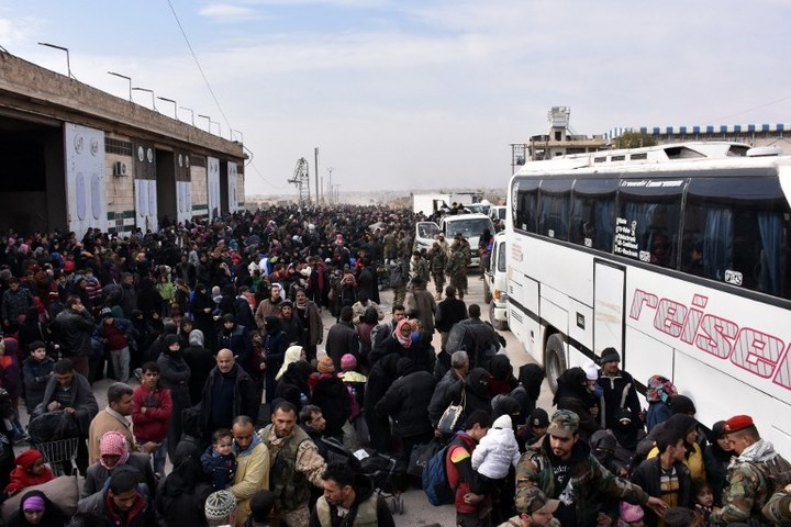 Syrian families, fleeing from various eastern districts of Aleppo, queue to get onto governmental buses on November 29, 2016 in the government-held eastern neighbourhood of Jabal Badro,