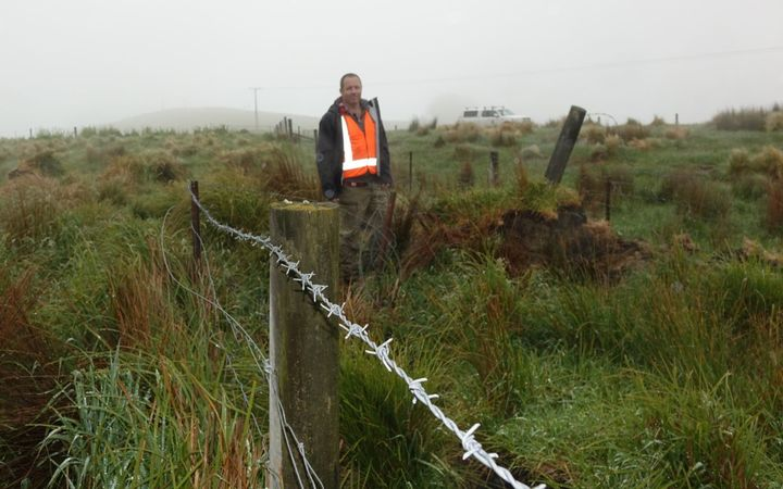Adrian Benson stands beside a fence that was once straight.