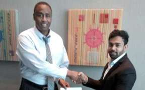 The founder of Instacharge, Douglas Stewart, left, meets with businessman Gaurangbhai Patel in Fiji last week