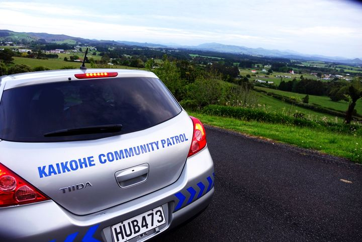 A silver community watch patrol car, perch on a hill about a farm. Locals patrol the region doing work they say the police should be doing
