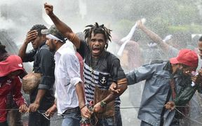 Protesters are resisting police using water cannons during a protest by mostly university students from Free Papua Organization and the Papua Student Alliance in Jakarta on December 1, 2016.