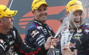Shane van Gisbergen cops a faceful of champagne on the podium.