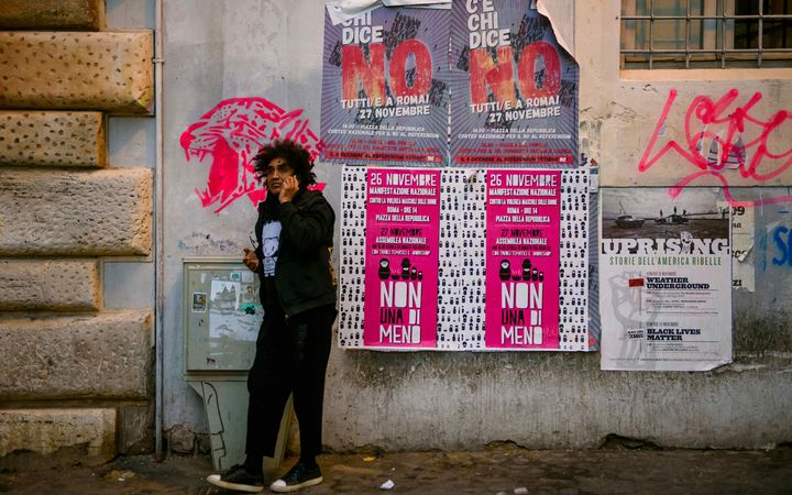 A man telephones while standing in front of posters belonging to the 'No' campaign ahead of the upcoming referendum to amend the Italian constitution.