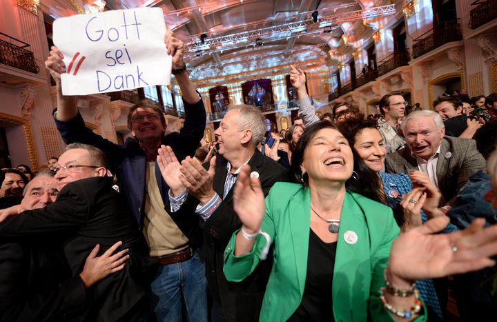 "Supporters of Alexander Van der Bellen,one holding a sign reading ""Thank God"", celebrate as early results come in."