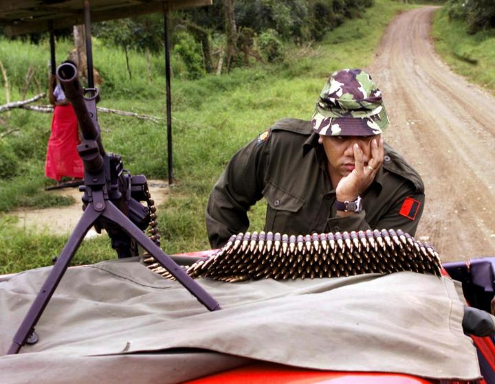 A soldier guards the road to Nasova village after a soldier and a policeman were killed in an ambush by the last rebel supporters of coup leader George Speight in Fiji 2000.