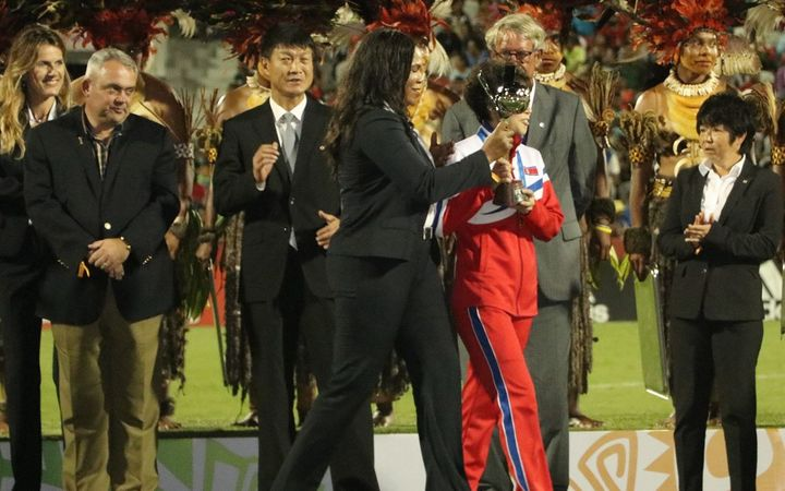 PNG Sports Minister Justin Tkatchenko (L) watches on as North Korea receive the FIFA Under 20 Women's World Cup trophy.