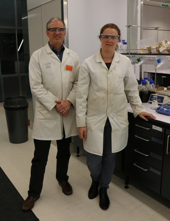 An image of Professor Paul Kilmartin and PhD student Charlotte Vandermeer wearing white coats and safety glasses, standing in the wine waste laboratory.