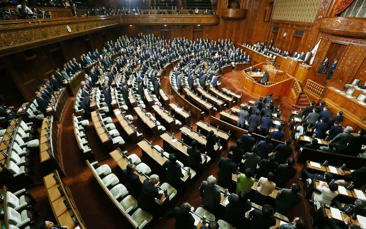 Ruling coalition lawmakers stand to approve the passage of the Trans-Pacific Partnership free trade deal in the lower house of the parliament in Tokyo.