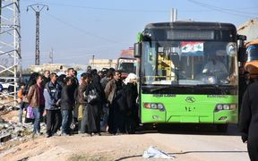 Syrian residents fleeing the violence, queue as they board a bus at a checkpoint, manned by pro-government forces, in the village of Aziza on the southwestern outskirts of the northern Syrian city of Aleppo