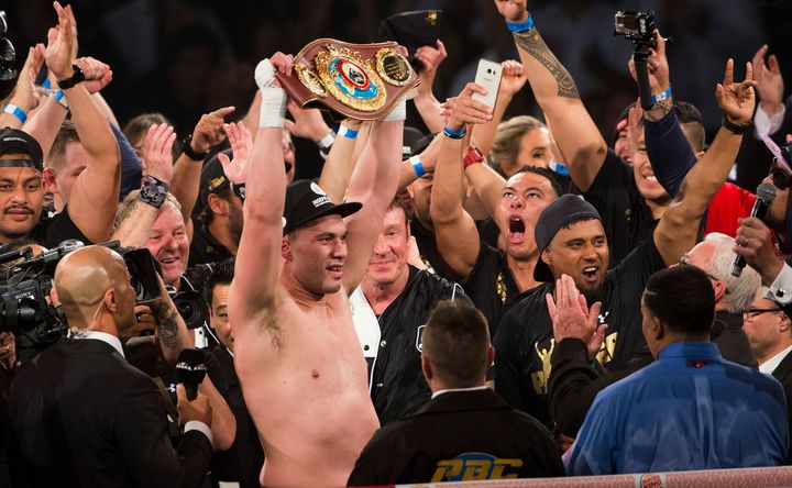 New Zealand heavyweight Joseph Parker holds up the WBO belt alongside his team.