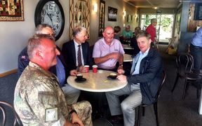 Prime Minister Bill English (far right) takes a break at a local cafe in Kaikōura.