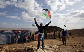 A Palestinian man raises the national flag in front of Jewish settlers during a demonstration by Palestinian and Israeli activists against the construction of Jewish settlements in the village of Ein al-Beida,
