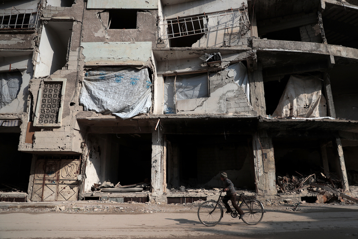A Syrian boy cycles past damaged buildings in the rebel-held town of Douma, on 30 December 2016, on the first day of a nationwide truce.