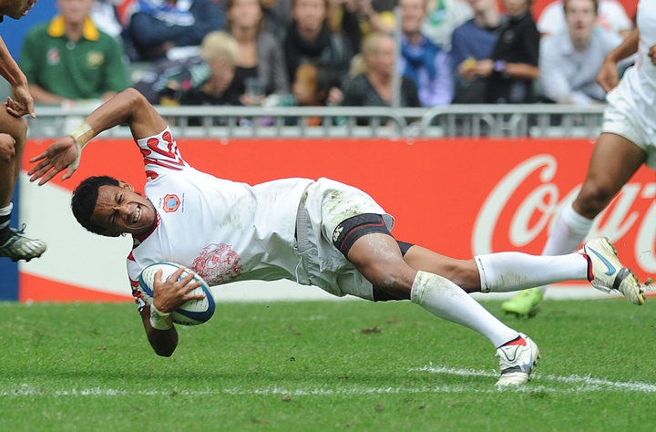Tongan Atelea Okati of Tonga falls to the ground with the ball under pressure from Li Jialin of China during their match at the Hong Kong Sevens rugby tournament in Hong Kong on 27 March, 2010. Okati died following a car crash in December 2016.