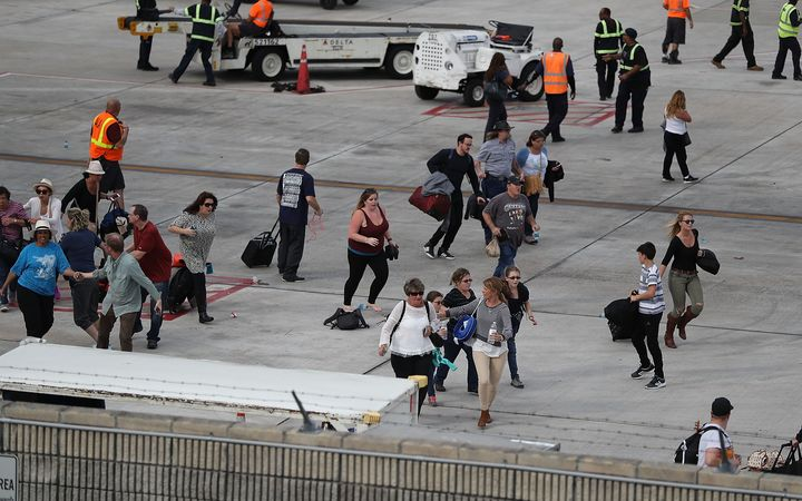 People seek cover on the tarmac of Fort Lauderdale-Hollywood International airport after a shooting took place near the baggage claim.