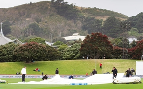 Groundsmen pull the rain covers on to the Basin Reserve.